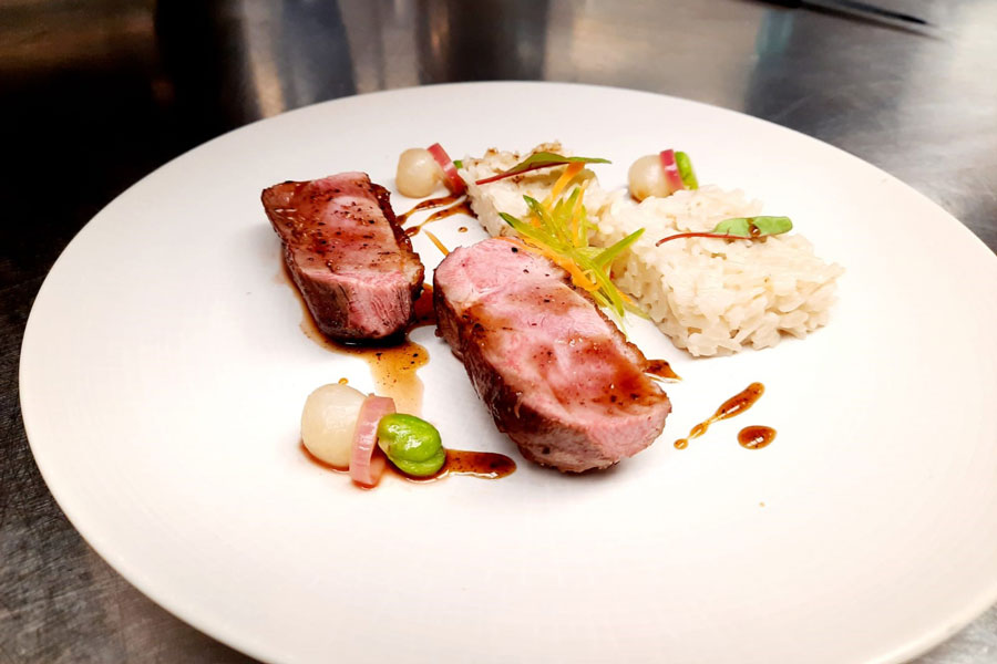 Honey and Szechuan pepper glaze duck breast with sticky coconut rice, broad beans, and stem ginger